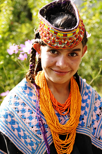 Kalasha girl with headdress and beaded necklace